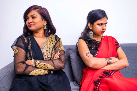 two young indian women in traditional sari and bindi looking in different sides in interior of living room