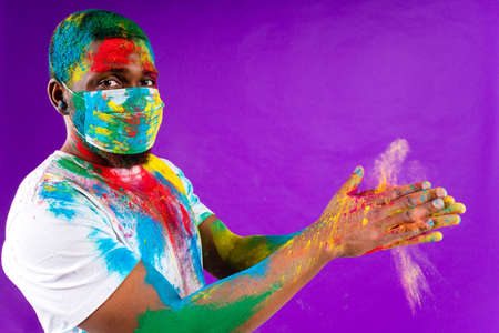 latin brazilian male in white cotton t-shirt with colorful paint of face laughing studio wear medical mask