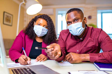 african american man and woman wear medical mask and stylish marsala jacket working online by laptop 版權商用圖片