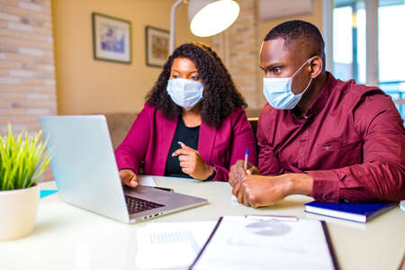 Authentic people african american man and woman wear medical mask and stylish marsala jacket working online by laptop