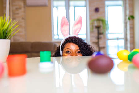 Authentic people african american woman hiding under the table on Easter in apartment