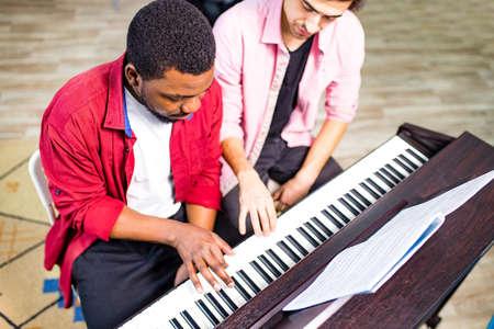 latin hispanic man learning to play on piano with caucasian teacher in classroom