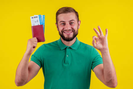 ortrait of a happy young man in sunglasses and green t-shirt holding passport isolated over yellow background