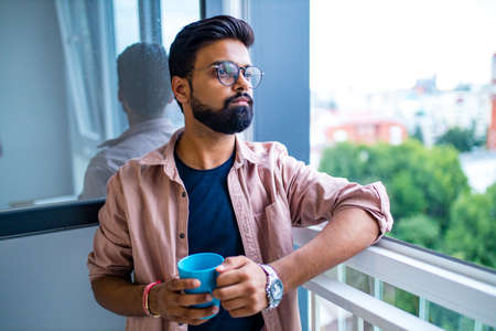 arabian man in casual dress holning a blue cup and looking dreamly
