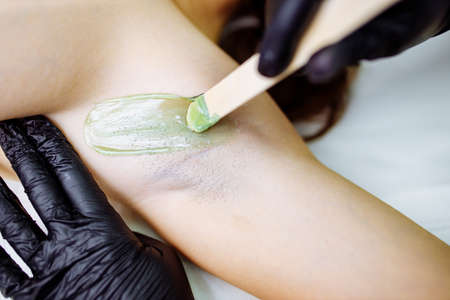 close up waxing arm paids area in studio spa