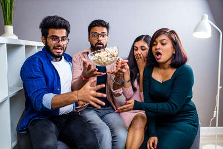 four indian friends watching cinema in the night time at home throwing popcorn Stockfoto