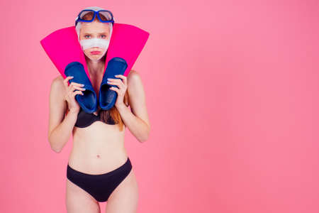redhaired ginger woman with a bandaged face holding flippers and looking sad in studio pink background