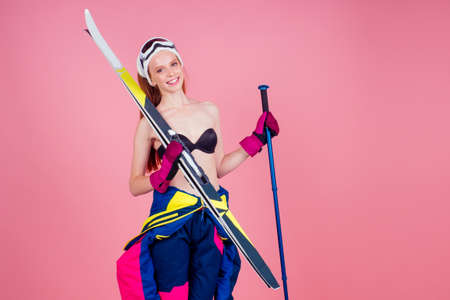 redhaired ginger young woman in bra top with skis posing in studio on pink background Stockfoto