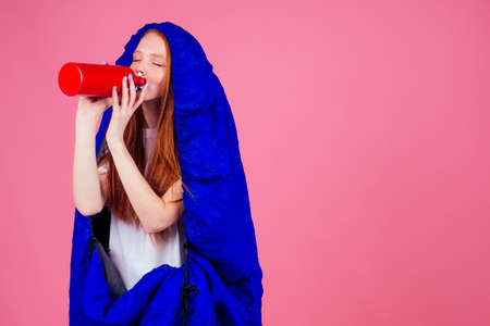 redhair ginger woman holding red   wrapped in in sleeping bag Stockfoto