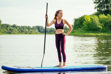 woman on sup sup board in nature at evening