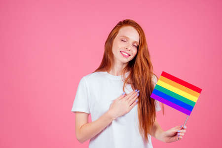 redhaired ginger woman in white casual t-shirt holding rainbow flag in studio Stockfoto