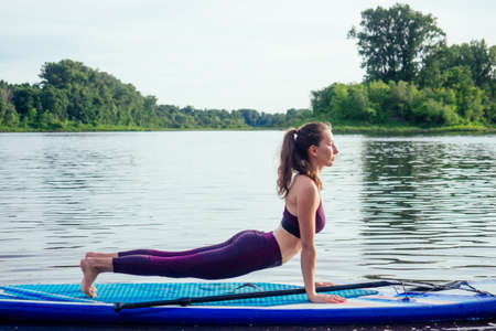Young woman doing yoga on sup board