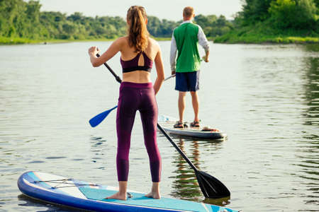Young attractive couple on stand up paddle board in the russian lake