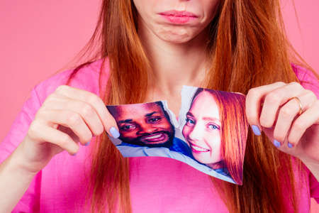 redhaired ginger woman in pink studio background tearing photo card of smiling international couple the end of the relationship Stockfoto