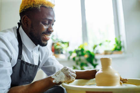 mixed race afro male potter with black apron sitting at workshop table potter