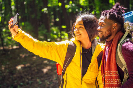 african american mixed race couple in forest making selfie Stockfoto