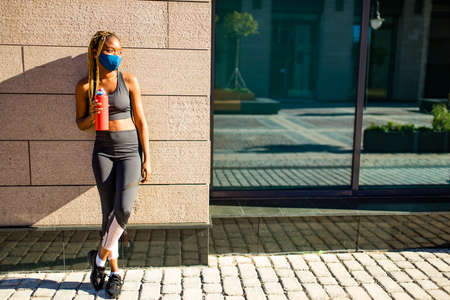 african american woman drinking smoothies after jogging in the downtown streets