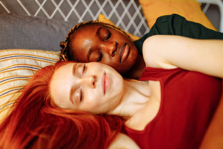cheerful afro and european women at home on the bed
