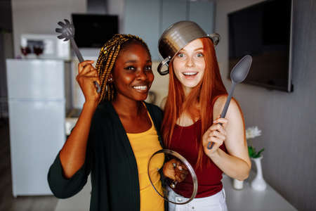 mixed race couple struggling with a saucepan on my head kitchen