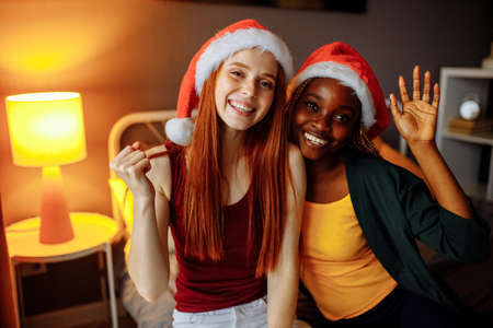 mixed race couple in santa claus hat at home in evening Stockfoto