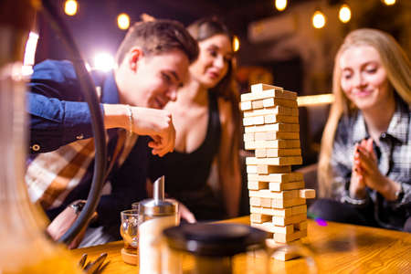 Young people have fun playing board games at a table Stockfoto