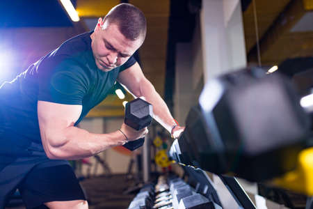Fit and muscular man trains with dumbbells in gym Foto de archivo