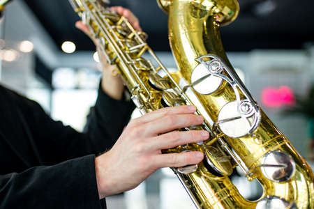 saxophone in hands close-up man in black outfit 版權商用圖片