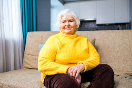 Thoughtful senior lady sitting at home with her fingers to her chin in living room 版權商用圖片