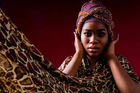 authentic mixed race boho fashion lady with makeup and silk turban over head in red studio background