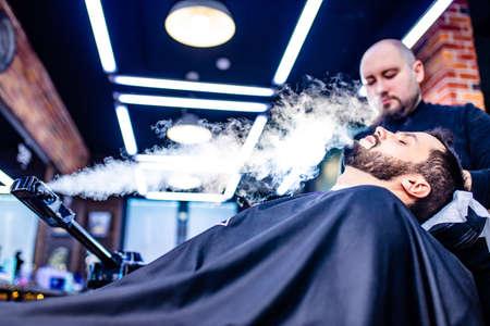 arabic handsome bearded man getting condensation moisture haircut at barbershop 版權商用圖片