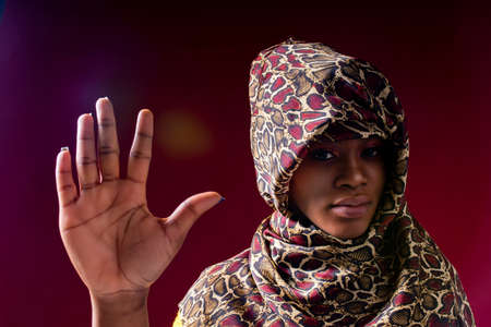 authentic mixed race arabian woman in leopard silk veil scarf hijab showing no hands sign