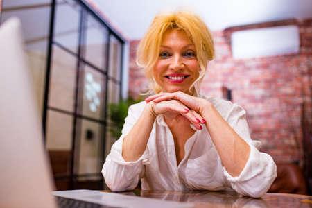 mature beauty woman in white silk luxury shirt in living room working 版權商用圖片