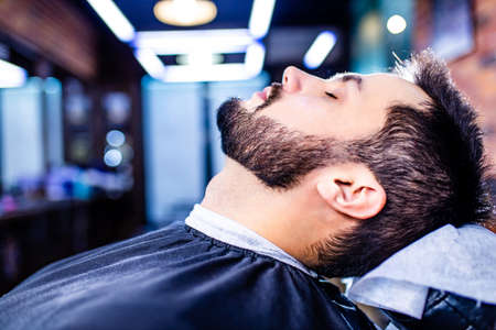 hispanic bearded man having his hair cut by hairdresser at the barbershop