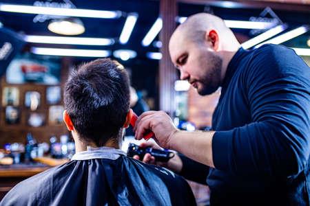 Hairstylist cutting hair of male customer at barber shop 版權商用圖片