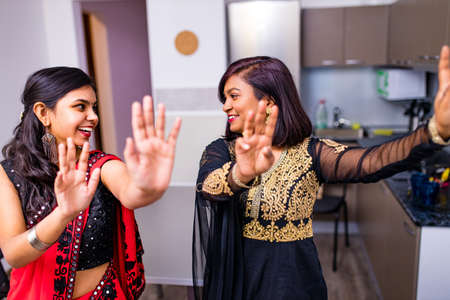 happy indian sisters are dancing together in new light apartment with design repair moving concept house