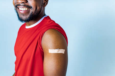 vaccinated mixed race showing an adhesive bandage on shoulder after injection studio background Imagens