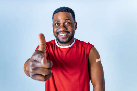 afro american sportsman showing his arm after receiving a vaccine in studio Stock fotó