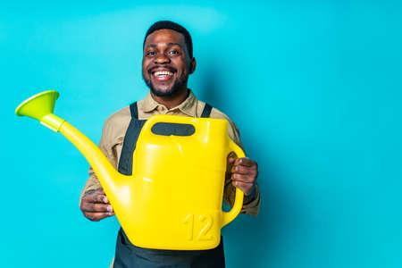 brazilian gardener man holding yellow watering can in studio blue background Imagens