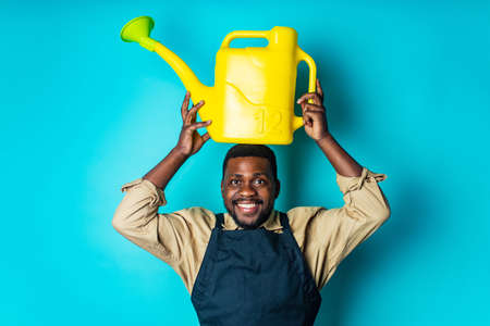 latino spain man in black apron holding yellow watering can in blue studio Imagens