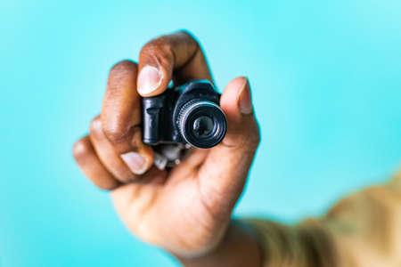 mini camera in hand of african american people in blue studio