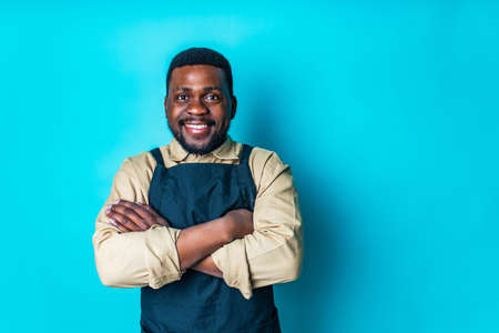 happy latin man in cotton shirt ant black apron in blue studio looking at camera and feeling good