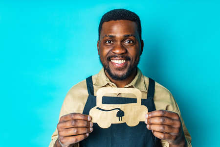 mixed race man holding paper car with recharging socket in blue studio background eco electro car concept