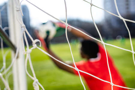 brazilian man goalkeeper catches the ball in the stadium during a football training