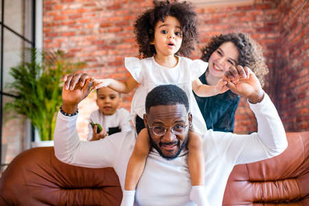 Happy family with two kids playing at home Imagens