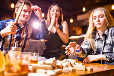 Young people have fun playing board games at a table .