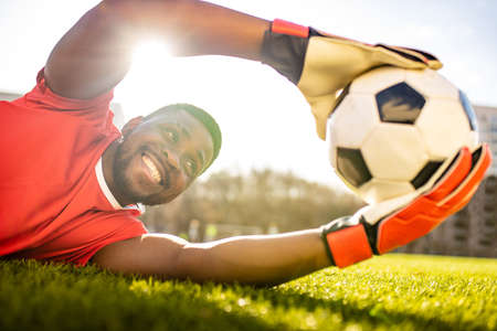 happy multicultural hispanic soccer player smiling and wear red sporty suit outdoor sunny day