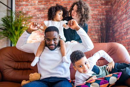 afro american mixed-raced family looking at camera in cozy summer day light in living room Imagens