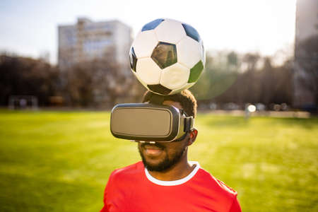 happy man in virtual reality glasses in football field background is blurred concept of virtual reality outdoors summer sunny day.