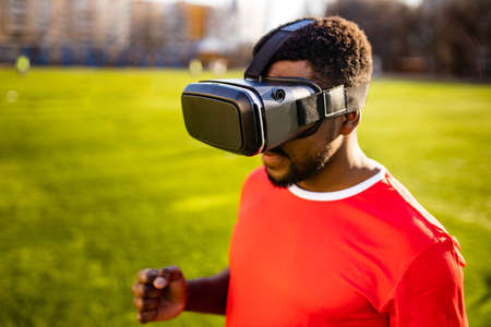 happy man in virtual reality glasses in football field background is blurred concept of virtual reality outdoors summer sunny day