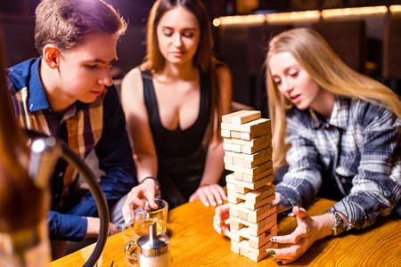 Young people have fun playing board games at a table Imagens